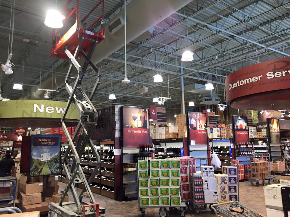 Image of a man on a scissor lift in stalling a pendant light at Elk Grove Total Wine.